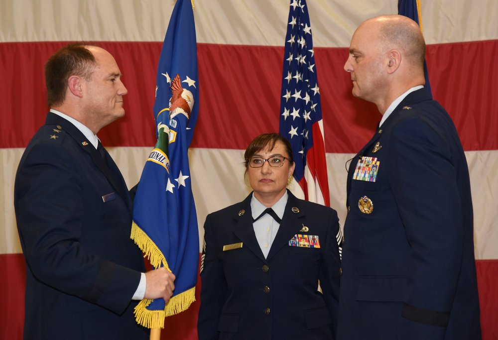 Brig. Gen. James R. Kriesel (right), incoming commander, Oregon Air National Guard, assumes command from Maj. Gen. Michael E. Stencel (left), Adjutant General, Oregon, as Chief Master Sgt. Ulana Cole, State Command Chief, looks on during a change of command ceremony at the Anderson Readiness Center in Salem, Oregon, Jan. 6, 2018. (U.S. Air National Guard photo by Tech. Sgt. Brandon Boyd, 142nd Fighter Wing Public Affairs)