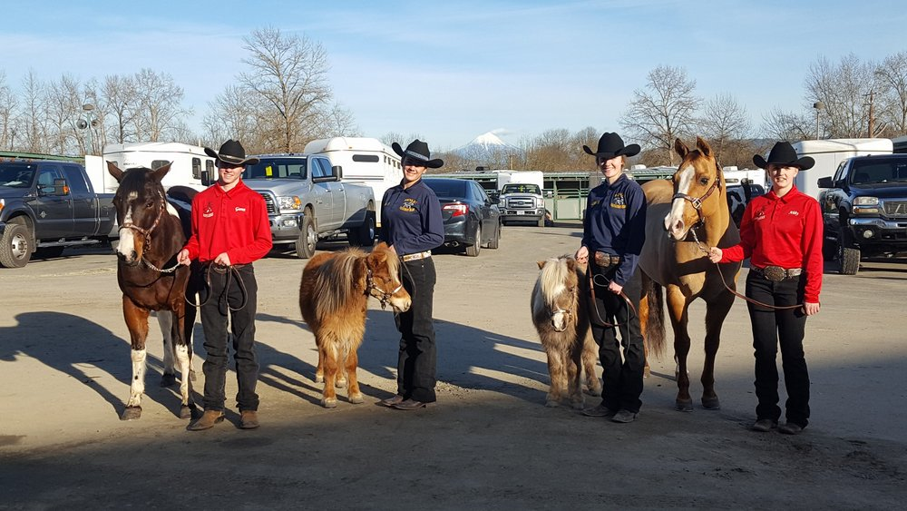 "Horsemen athletes get ready to partake in the ""In Hand Obstacle Relay"" at the Southern Oregon High School Equestrian Team Meet. Pictured left to right: Garret Fox (Bonanza HS), Lillian George (Henley HS), Kendal Griffith (Henley HS), and Abby Orella (Bonanza HS).  Image by Danielle George."