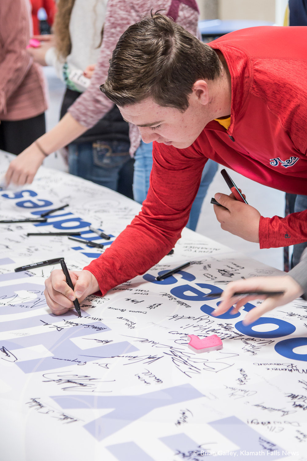 "Students sign a banner to be sent to Parkland High School. The banner reads - ""Henley High School Chooses Kindness.""  Henley High School student led assembly to walk up in support for Marjorie Stoneman DouglasHigh School rather than walking out in protest of Gun Control honored the 17 lives lost at the Parkland Shooting. March 14, 2018. (Brian Gailey)"