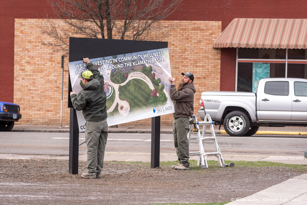 Richard Welsh and Mike Stilwell of Modoc Contracting install new signs at the newest park in downtown Klamath Falls. March 15, 2018 (Brian Gailey).