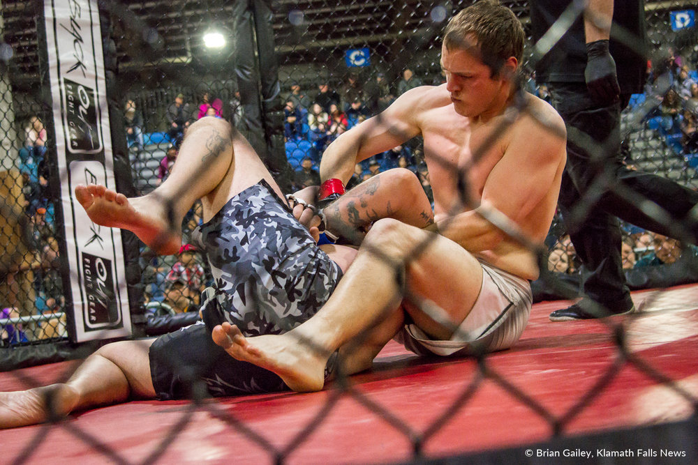 Fighters battle inside the MMA Cage during Arena Wars at the Klamath County Fairgrounds.March 24, 2018 (Brian Gailey)