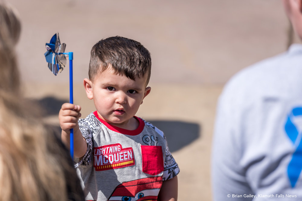 A child stands with a blue pinwheel among 200 inside Sugarman's Corner in Downtown Klamath Falls to celebrate a Day of Hope. Hope that child abuse can be eradicated. April 4, 2018 (Brian Gailey)