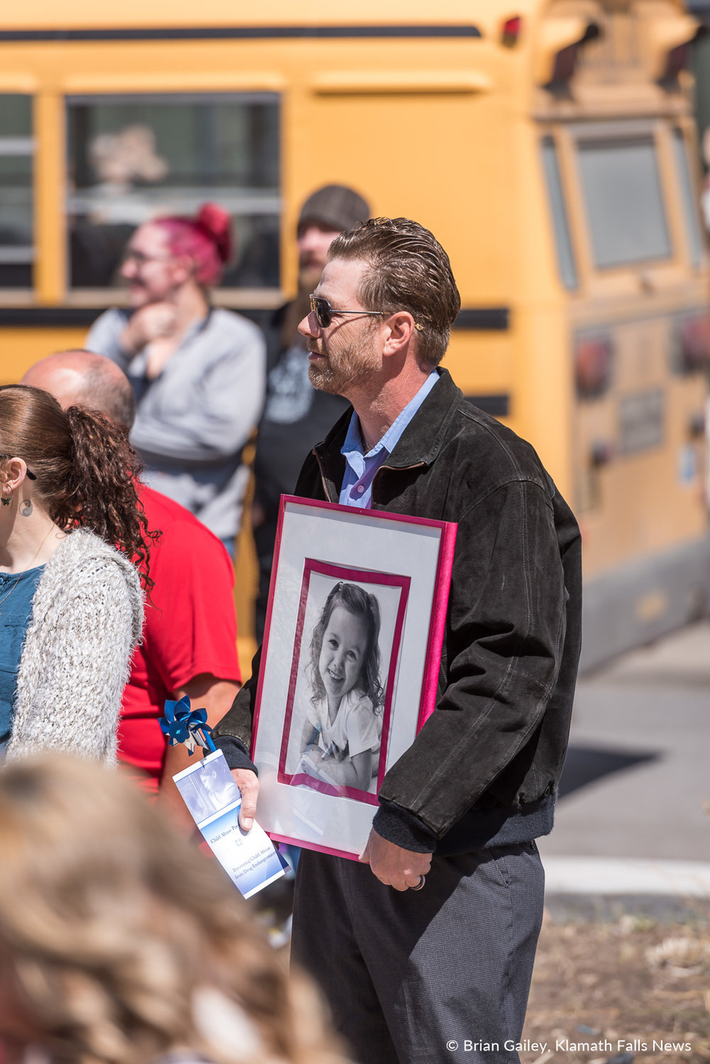 A man stands with a portrait of a child 200 inside Sugarman's Corner in Downtown Klamath Falls to celebrate a Day of Hope. Hope that child abuse can be eradicated. April 4, 2018 (Brian Gailey)