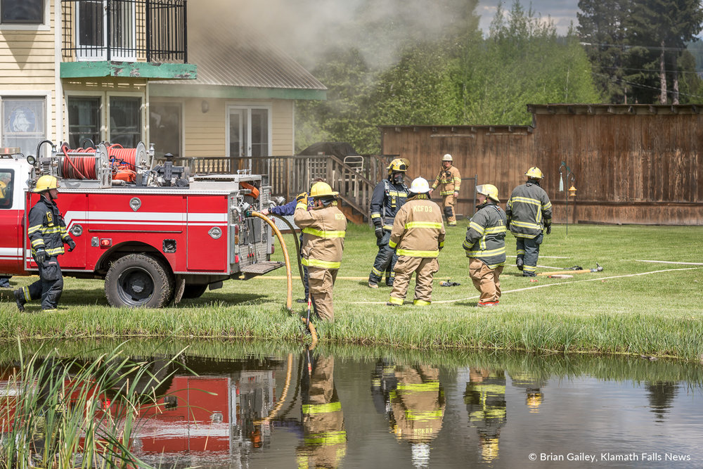 A Chiloquin Fire and Rescue truck pumps water from a pond to aid extinguish fire at the Crater Lake Bed and Breakfast. May 19, 2018. Image, Brian Gailey.
