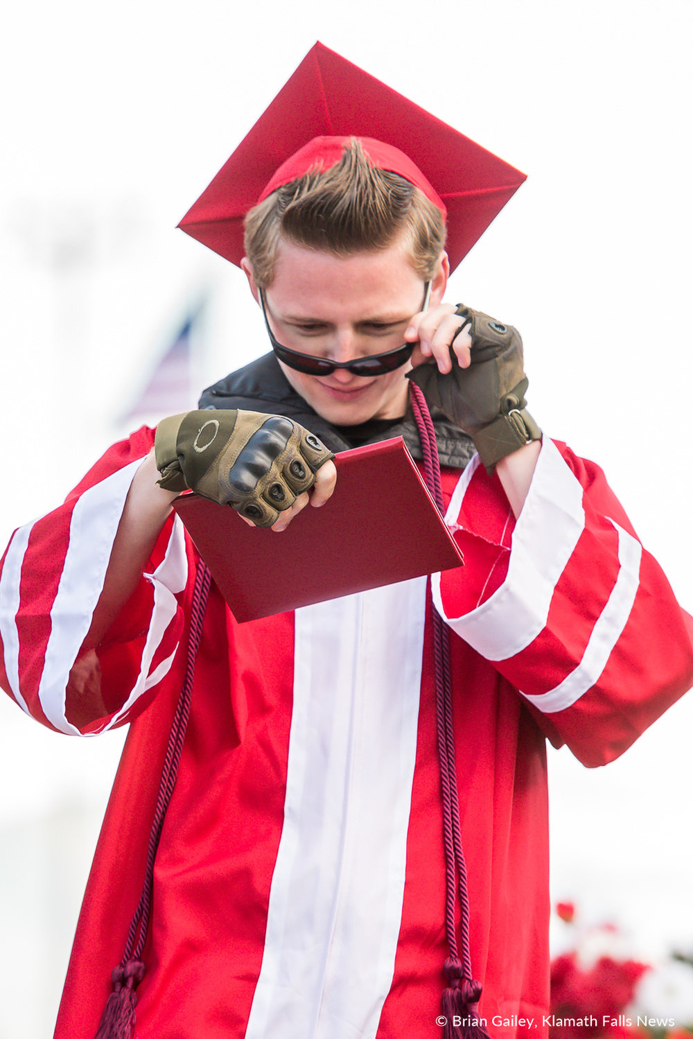 A KUHS graduate walks across the stage examining the diploma to make sure it is real. June 9, 2018 (Brian Gailey).