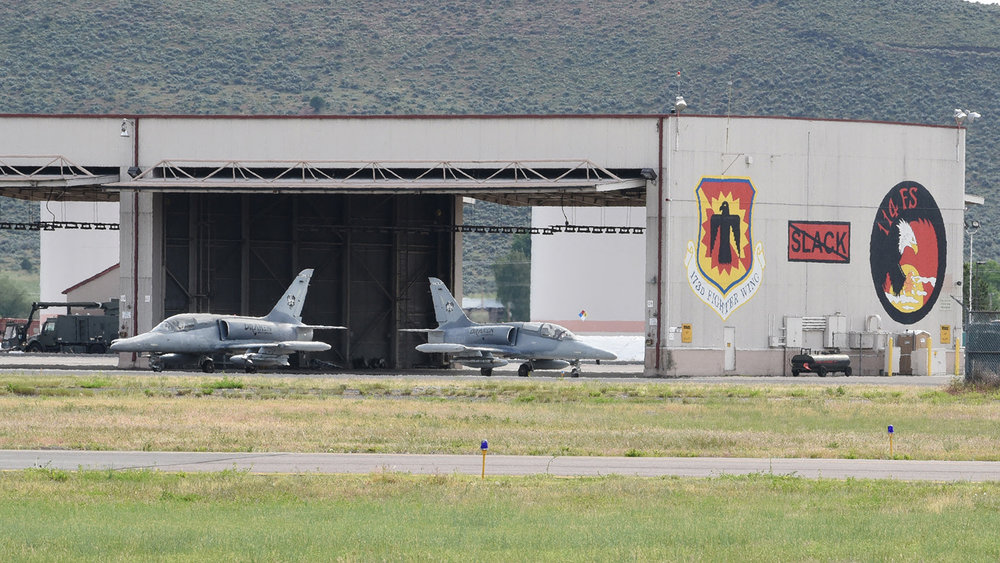 Two Draken contract L-156E Honey Badger aircraft taxi in front of the distinctive murals at Kingsley Field, in Klamath Falls, Ore., June 5, 2018. The 173rd Fighter Wing's day-to-day flying doesn't involve any other airframes, until now, as this contracted service is integrated into flying operations, simulating adversary aircraft and freeing its F-15 Eagles to carry more student pilots on training flights. (U.S. Air National Guard photo by Tech. Sgt. Jefferson Thompson)