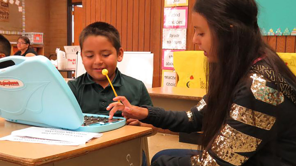 Ashley Nuno, 15, a sophomore at Lost River High School, helps her brother, Daniel Lara, 8, with the xylophone lesson in Sharon Cosand's second-grade class. Nuno, who is volunteering at the summer school, wants to be a kindergarten teacher. (Marcia Schlottmann, KCSD).