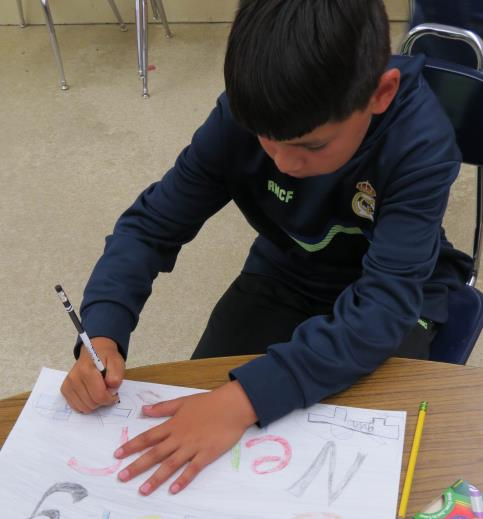 Brian Leon, 11, works on a gun safety poster, which will be displayed at Oregon Institute of Technology. He voluntarily attends migrant summer school to improve his reading skills.(Marcia Schlottmann, KCSD).