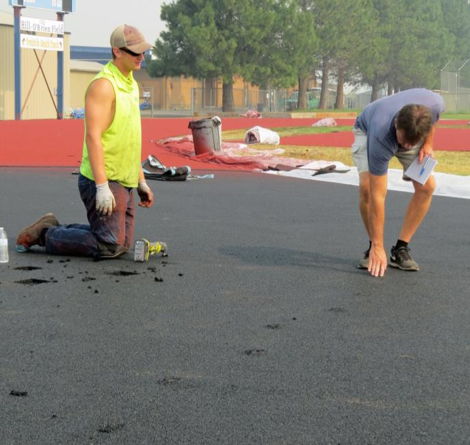 Henley High School Principal Jack Lee examines deer prints in the new track at Henley High School. Ian Luper of Beynon Sports is removing them.