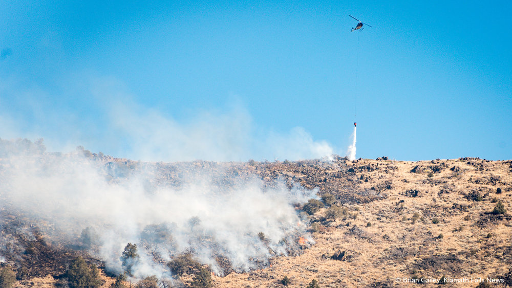 A helicopter drops water on the leading southern edge of the Stukel Fire. October 15, 2018 (Brian Gailey)