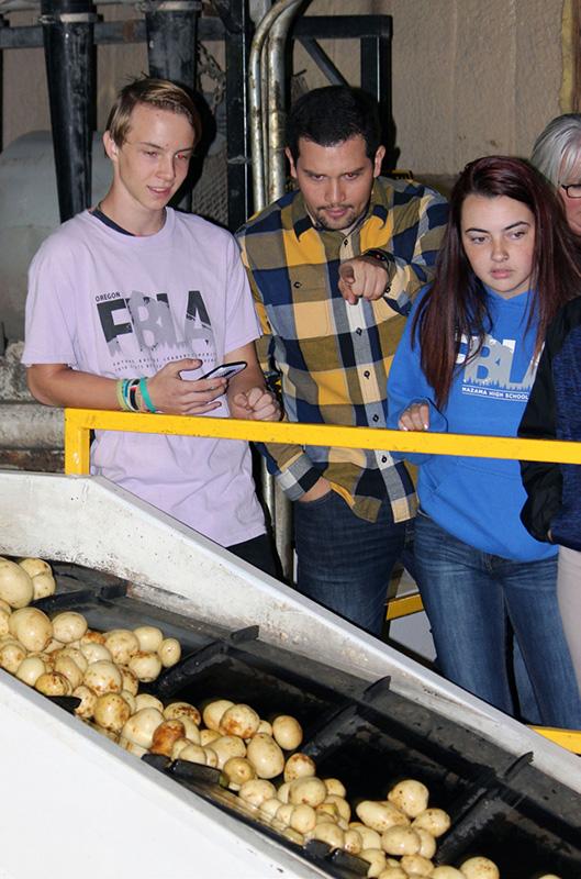 Mazama FBLA student Sebastian Short, Mazama business teacher Sergio Cisneros and Mazama FBLA student Kara LaMere take a tour of the processing facility at Gold Dust Potatoes.