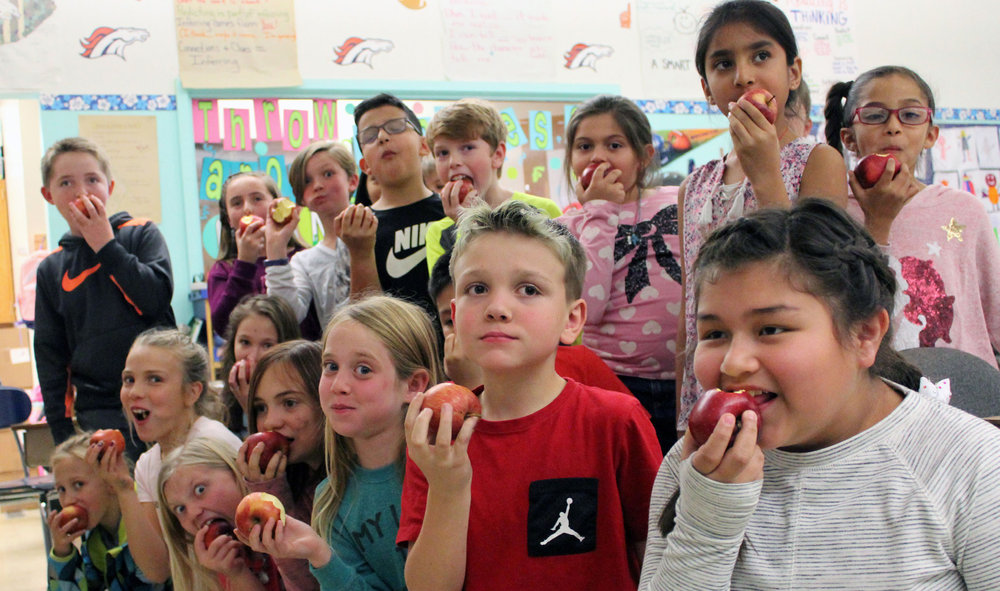 Students in Dena Morosin's fourth-grade class at Shasta Elementary School take bites of their apples during the Crunch At Once event Tuesday.
