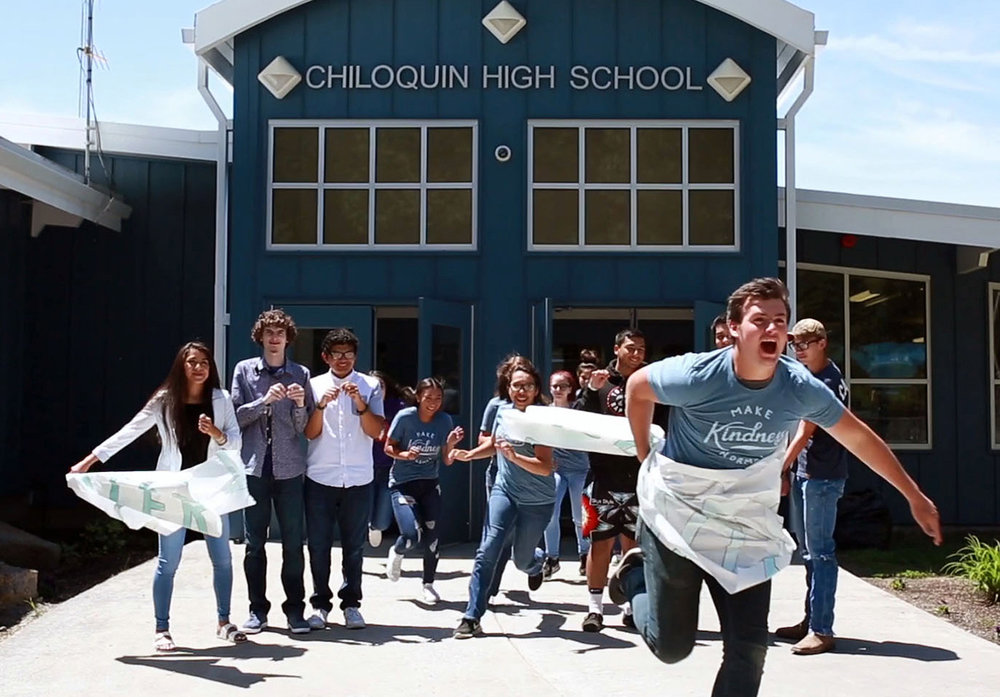 """Busting through stereotypes: An image in a video created by Chiloquin leadership students last spring shows students running through a sign stating """"Chiloquin stereotypes."""