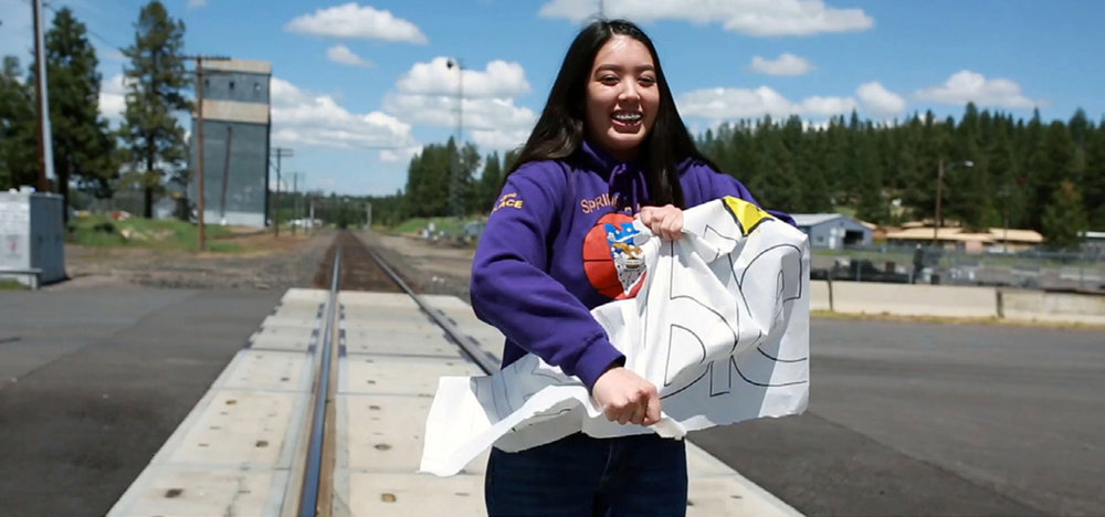 """Chiloquin junior Lani Jackson tears apart a sign stating """"Trouble"""" in a video created by leadership students last spring."""