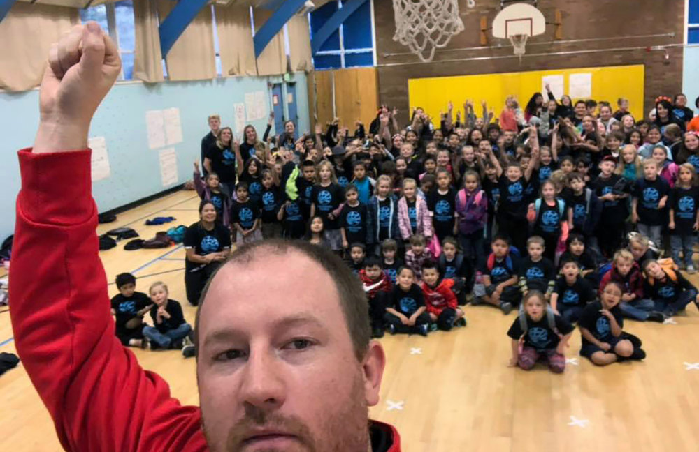 """Jordan Osborn, Chiloquin Junior-Senior High School vice principal and student leadership advisor, rallies students at Chiloquin Elementary School after giving them their """"Chiloquin Rising"""" T-shirts."""