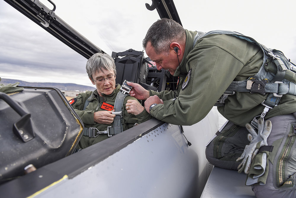U.S. Air Force Col. Jeff Smith, 173rd Fighter Wing commander, right, helps Secretary of the Air Force, Heather Wilson strap into an F-15D Eagle before a familiarization flight Nov. 4, 2018, at Kingsley Field in Klamath Falls, Ore. The secretary's visit provided her a first-hand look at the wing's mission as the sole provider of F-15C air superiority pilots to the U.S. Air Force. (U.S. Air National Guard photo by Staff Sgt. Riley Johnson)