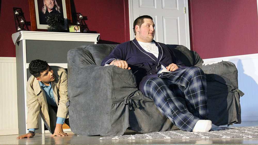 Detective Jack Sparks (Victor Manzo), while hiding behind the couch, overhears a conversation between Claude Purdy (Justin Ormsbee) and Patricia Purdy (Nicole Cleland), not pictured.