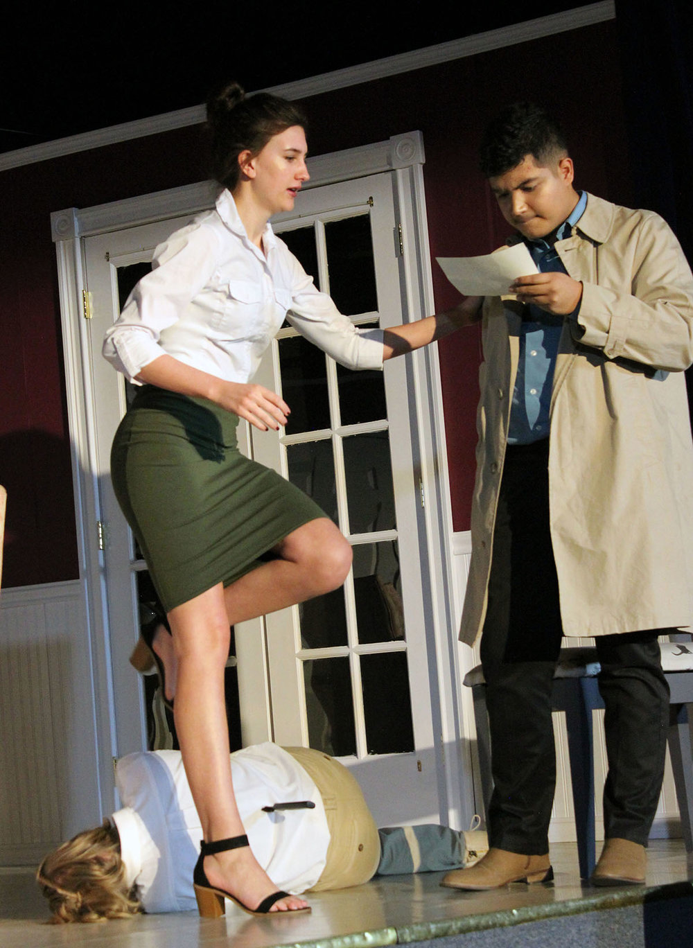 During a scene in Henley High School's production of Murder Runs in the Family, Heather Pallfeather (Kate Harter) steps over a murdered Western Union messenger (Haley Braswell) to read the message being held undercover detective Jack Sparks (Victor Manzo).