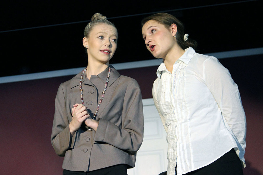 Matriarch and widow, Mirium Pallfeather (Brianna Eichelkraut), talks with her butler Montgomery (Elle Larson) during a scene in Henley High School's production of Murder Runs in the Family.