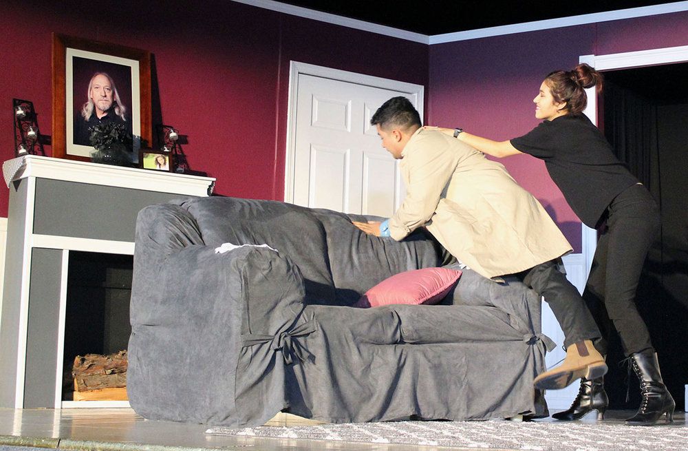 Maxine Pallfeather (Esme Murillo) throws detective Jack Sparks (Victor Manzo) over the couch while demonstrating her knowledge of martial arts during a scene in Henley High School's production of Murder Runs in the Family.