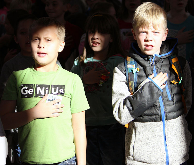 Peterson Elementary School third-graders Joshua Myrstol and Calian Silver put their hands hand over their hearts as they say the Pledge of Allegiance during a Veterans Day assembly on Friday.