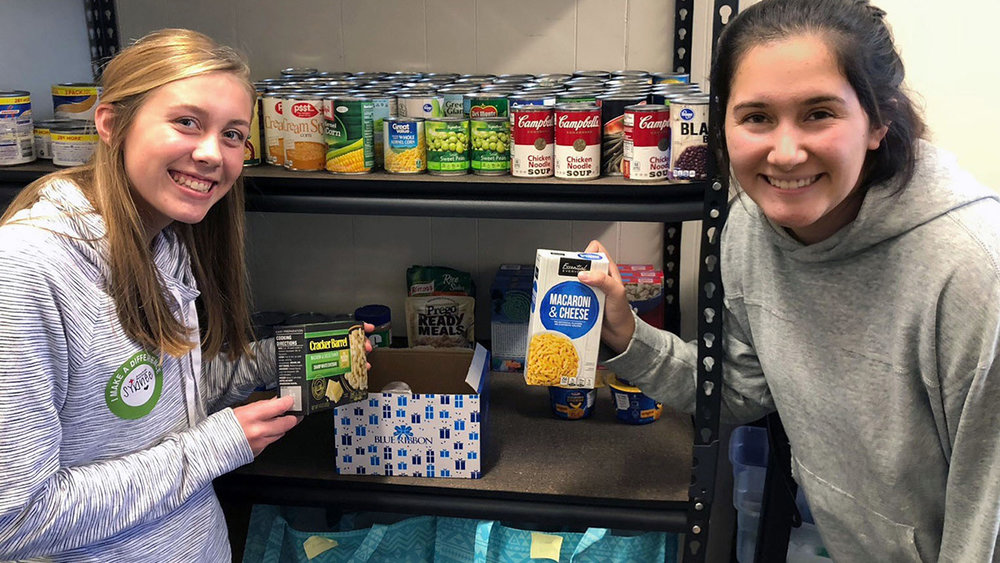Henley High School seniors Macy Hullman and Sophia Gomez show some of the items in the school's food pantry as part of the program Hunger: Not Impossible.
