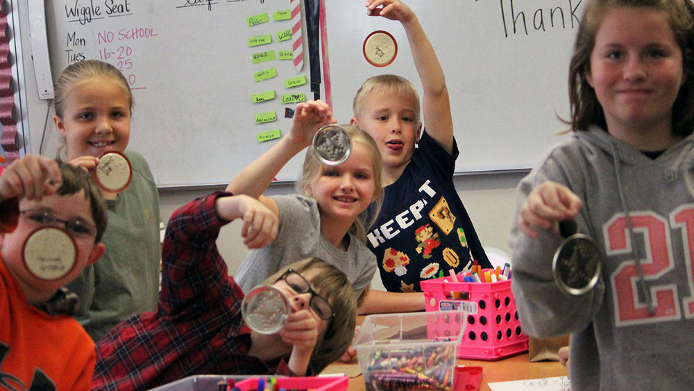 Henley Elementary School fourth-graders (from left) Gaines Cleland, Payton Case, Maddox Duren, Brynne Hedlund, Gunnar Olin and Jalena Elko show off their tin star Christmas ornaments they made during Pioneer Day.