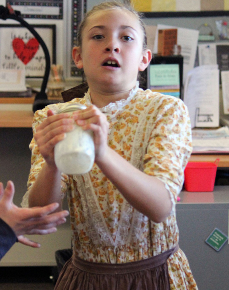 Henley Elementary School fourth-grader Samantha Cunningham shake mason jars of heavy cream to make butter during the school's annual Pioneer Day.
