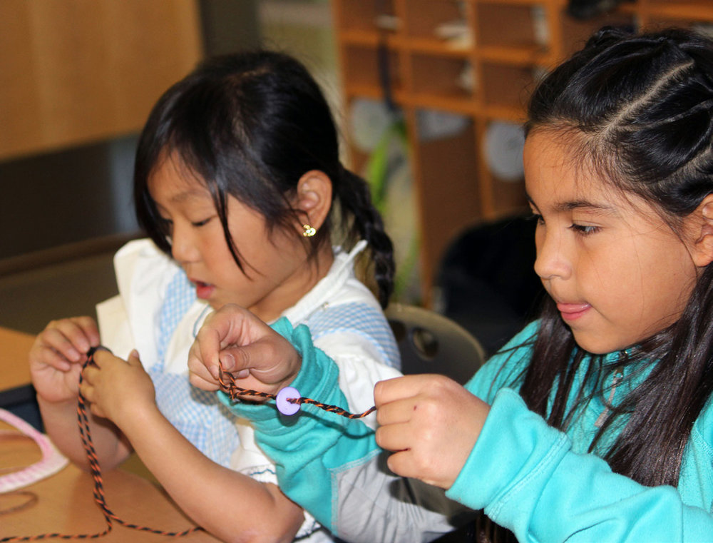 Paige Vradenburg and Sayuri Serrano Lopez make whirly gigs during Henley Elementary School's Pioneer Day.