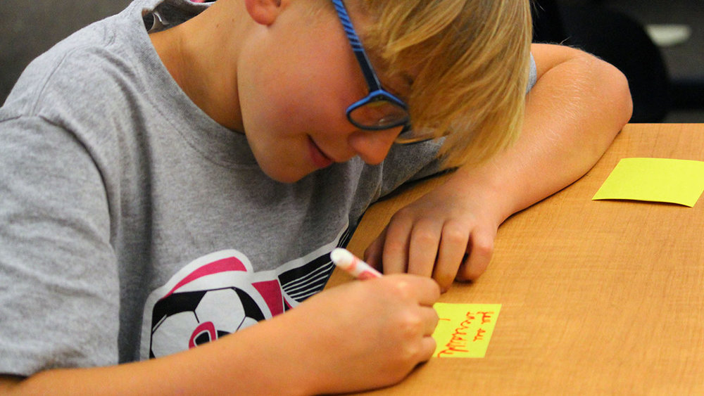 Luke Balzotti writes kind notes to classmates during the first Kindness Club meeting at Henley Elementary School.