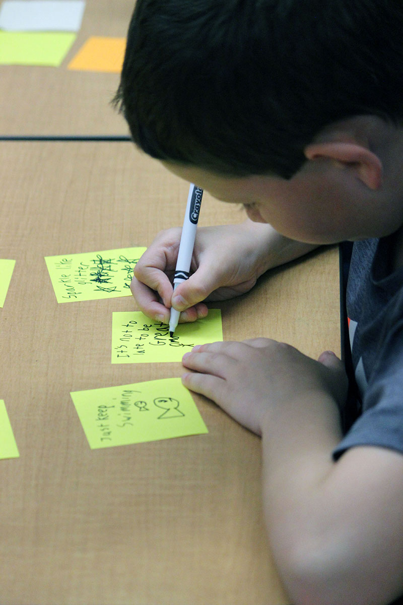 Brennan McFall write and pass out kind notes to classmates during the first Kindness Club meeting at Henley Elementary School.