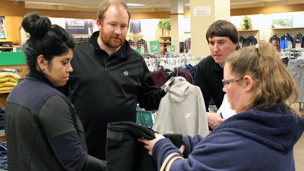 Jordan Osborn, vice principal, and Andy Davis, academic learning facilitator, talk with friends senior Dan Jones recruited to help make purchases at Fred Meyer.
