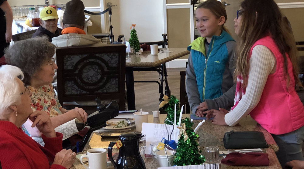 Bonanza Elementary School students Emma DeJong and Jean Wall visit with senior living residents at Pacifica Senior Living.