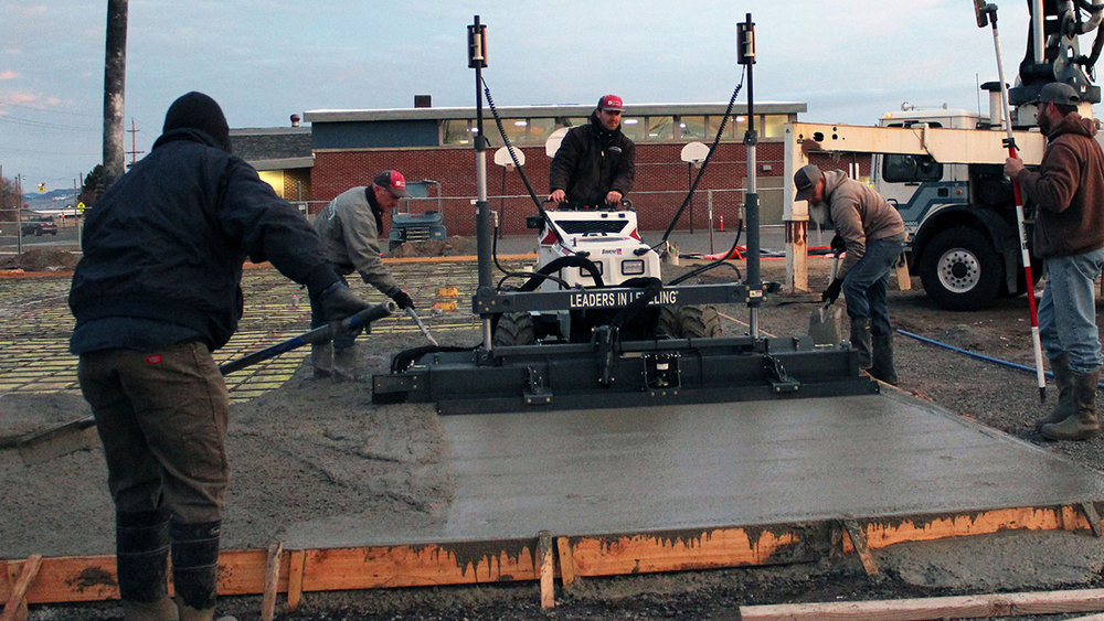 Dan Kinsman and Brian Kinsman, owners of Kinsman Concrete, operate the laser screed during the concrete pour of the foundation of Henley Middle School's new classroom building.