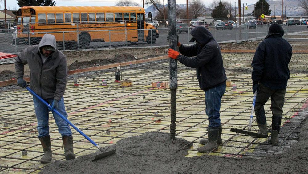 KCSD's Glenn Tillery and Eduardo Ramirez work the concrete as a school bus passes by.