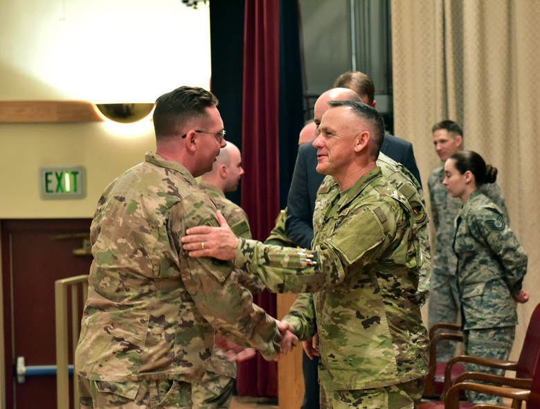 U.S. Air Force Chief Master Sgt. Mark McDaniel, the command chief for the Oregon Air National Guard, congratulates Senior Airman Jacob Enyart of the 270th Air Traffic Control Squadron during a demobilization ceremony, Jan. 4. He and 14 other Airmen departed for Al Asad Air Base in Iraq in the Spring of 2018 and returned six months later after performing contingency air traffic control operations. (U.S. Air National Guard photo by Tech. Sgt. Jefferson Thompson)