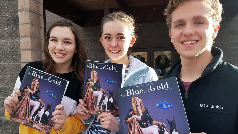 """Co-editors Danielle Herinckx, Sophie Kenney and Jabul Rasmussen of Henley High School's new quarterly magazine """"The Blue and Gold"""" show off copies they picked up from the printer Friday."""