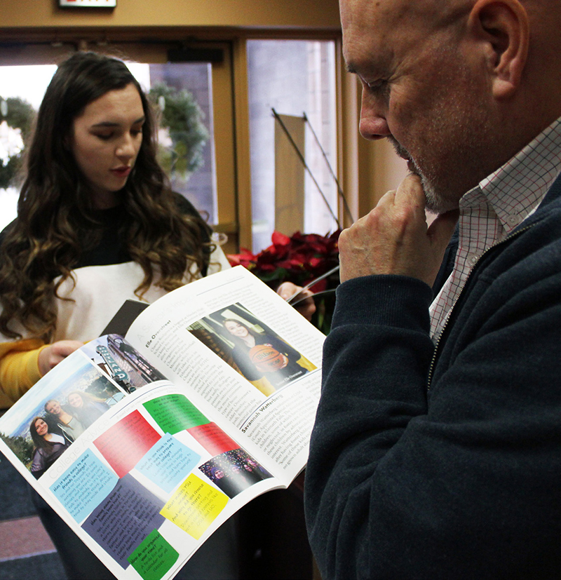 """Co-editor Danielle Herinckx and media class teacher Robert Chambrose look through copies of the first edition of """"The Blue and Gold."""" Chambrose co-teaches Henley's new media class with Carlos Becerra."""