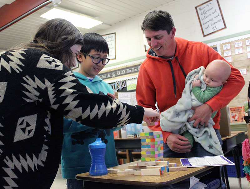 Fifth-grader Wyatt Snodgrass plays a game of color-coded Jenga with his father, Mike Snodgrass (holding baby Oliver), and teacher Anna Monteil.