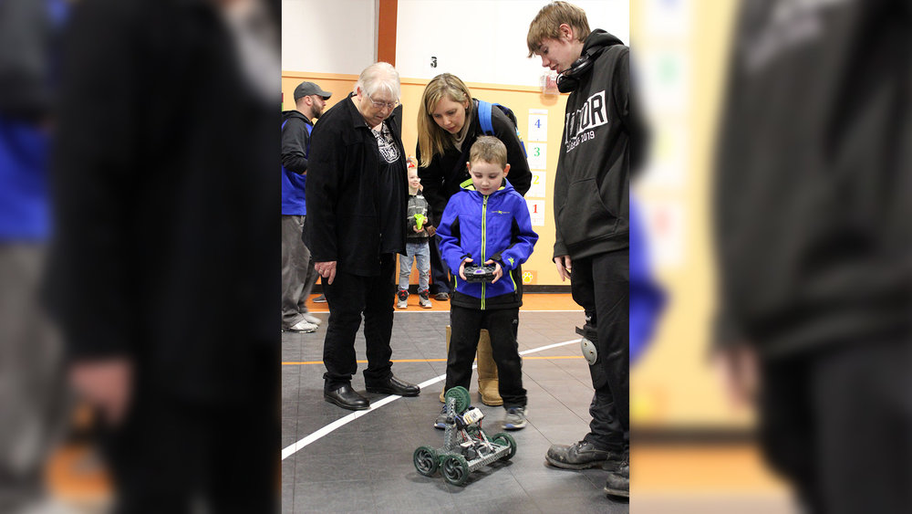 Mazama STEM&M student Jeremy Mathews helps Cedric Reid use a remote control to drive a robot while Cedric's grandmother, Lila Dickinson, and mother, Laura Reid, watch.