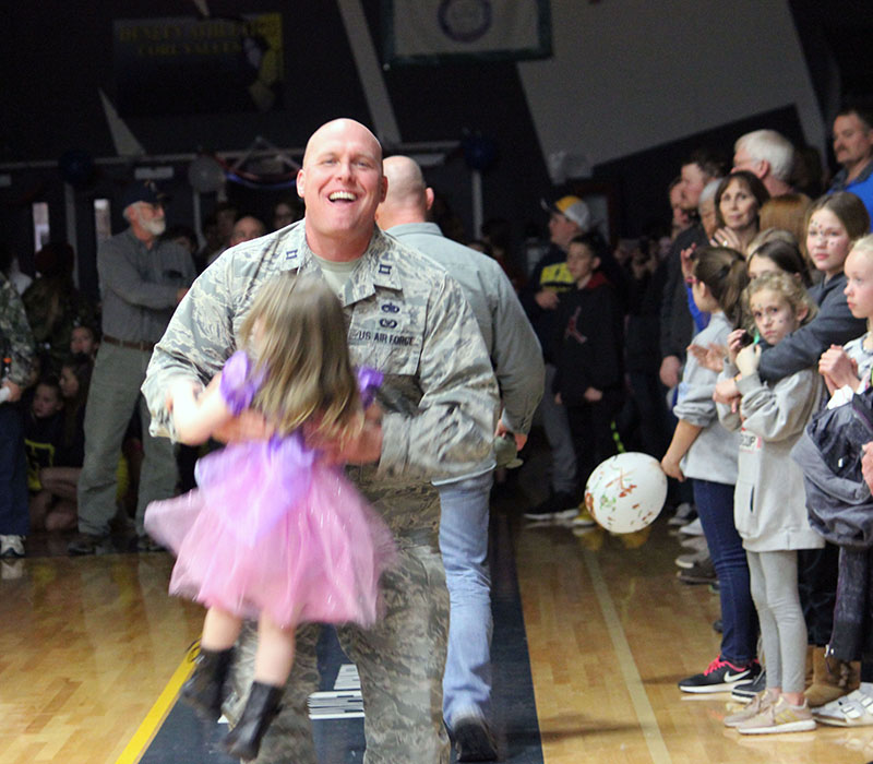 Capt. Rich Schuster of the 173rd Fighter Wing at Kingsley Field turns around and hugs his young daughter who followed him from the stands as he started to join fellow veterans and active duty military members who were being honored Feb. 5 during Henley High School's Military Appreciation Night.
