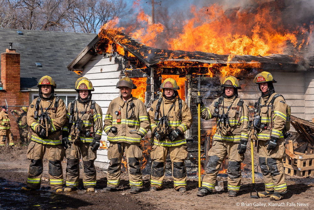 Klamath County Fire District 1 held a burn to learn for student firefighters. Pictured here are Kyle Brink, Jared Hoopers, Justin Llanes, Jacob Conley, Brett Doshier and their instructor, Dave Sonneman. The class took a moment for a group photo in front of the home that was donated for the training exercise by Power Pac Rentals and Sales. March 14, 2019 (Brian Gailey / Klamath Falls News)