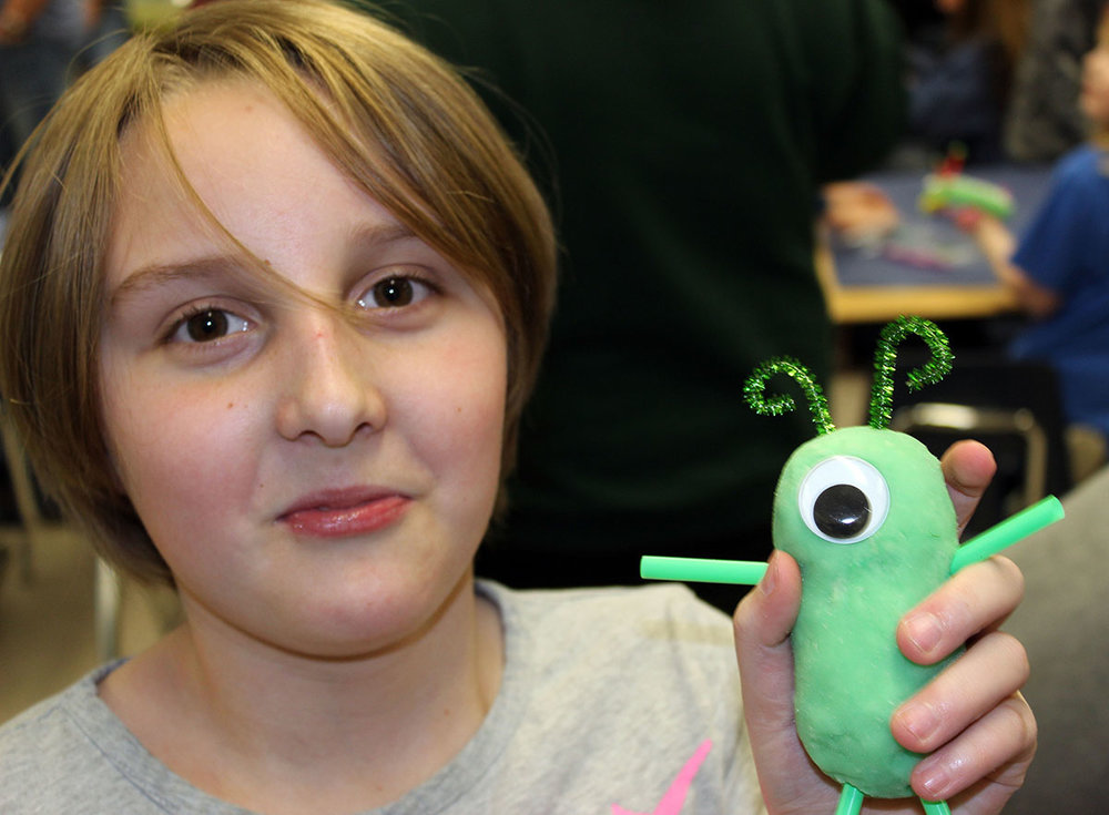 """Emma Van Leuven poses with her """"monster"""" following a creative activity during Peterson's Family Literacy Night. (Image: Jennifer Hawkins)"""