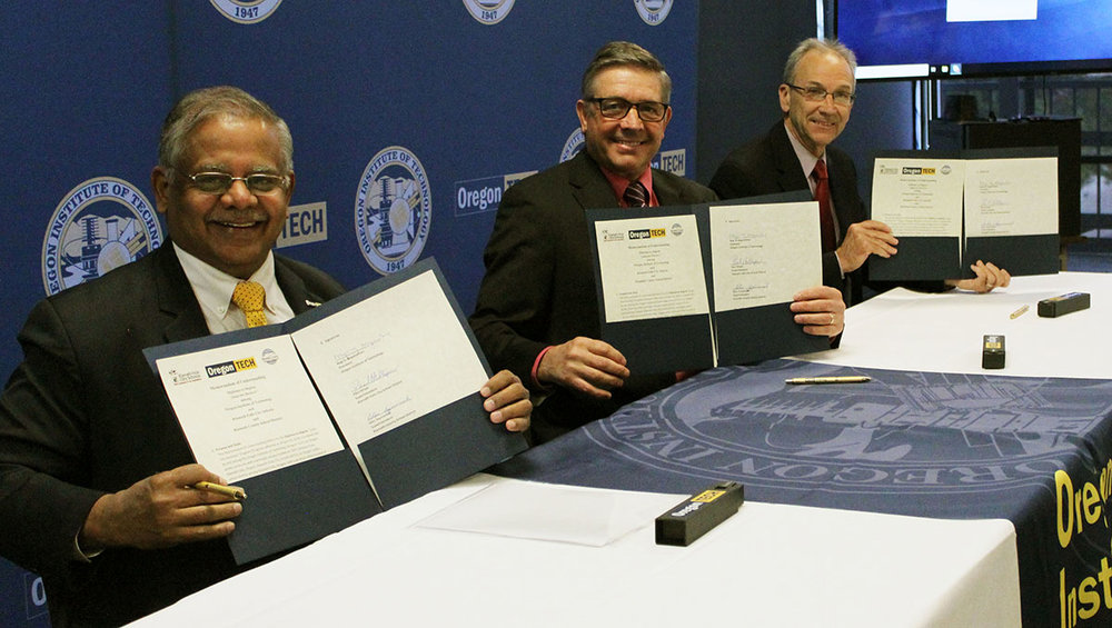 Oregon Tech President Dr. Nagi Naganathan, Klamath County School District Superintendent Glen Szymoniak, and Klamath Falls City Schools Superintendent Dr. Paul Hillyer display the memorandum of understanding they signed Wednesday for a new business academic pathway.