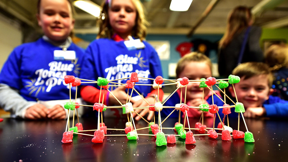 Kingsley Kid's Day brought children of base Airmen to the school room where they explored STARBASE curriculum like building a weight-bearing bridge using gum drops and toothpicks, which they tested immediately following the building, April 6, 2019 at Kingsley Field in Klamath Falls, Oregon. The program was designed to be a day of science, technology, and math exposure in a fun, hands-on environment and ended with a presentation by a senior officer to each of the children. (U.S. Air National Guard photo by Tech. Sgt. Jason van Mourik)