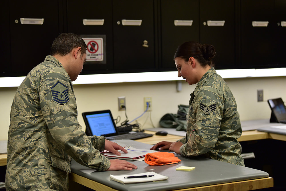 U.S. Air Force Master Sergeant Romero Castillo, AETC Inspector General, reviews paperwork from the 173rd Fighter Wing Aircrew Flight Equipment Shop, as Senior Airman Dakota Darling, 173rd FW AFE, observes during the Unit Effectiveness Inspection capstone event April 5, 2019 at Kingsley Field in Klamath Falls, Oregon. The capstone inspection is culmination of on ongoing virtual inspection on the effectiveness of the unit through four major graded areas—managing resources, leading people, improving the unit, and executing the mission. (U.S. Air National Guard photo by Airman 1st Class Adam Smith)