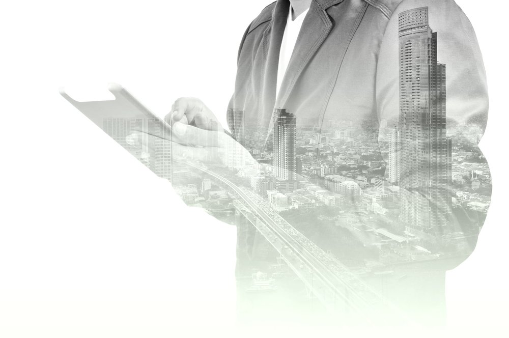 Double-exposure-of-city-and-Businessman-use-Tablet-device-505968136_2128x1413.jpeg