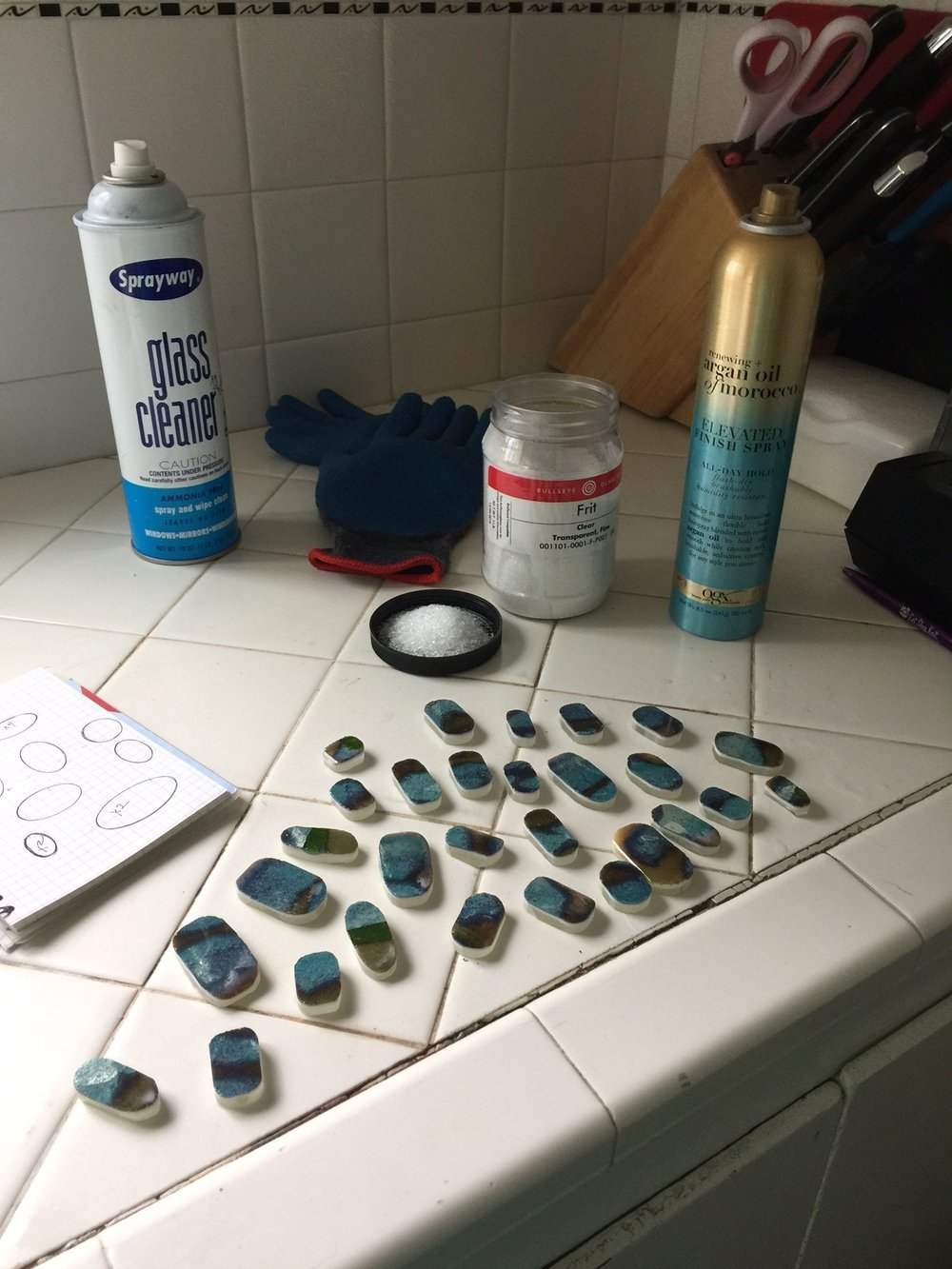 After I complete grinding, I clean the glass thoroughly with glass cleaner and microfiber cloth. I pour a quantity of fine clear frit into a small bowl and grab a can of cheap hair spray.