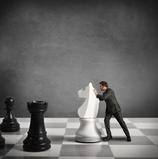 Man pushing pawn on giant chess board