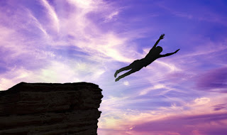 Person jumping off cliff and flying